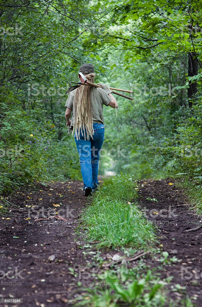 Farm worker walking away with tools over shoulder photo libre de droits