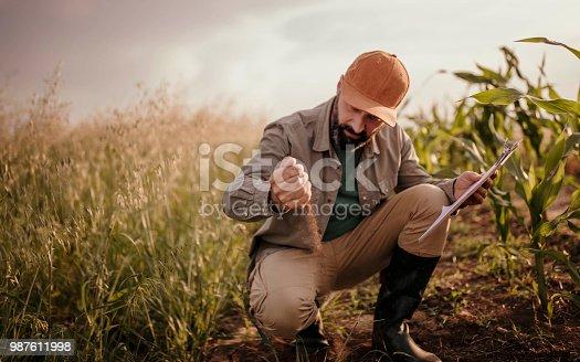 istock Farmer analyzes his land 987611998