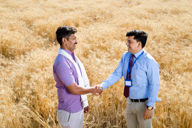 Farmer and businessman shaking hands in agricultural field stock photo