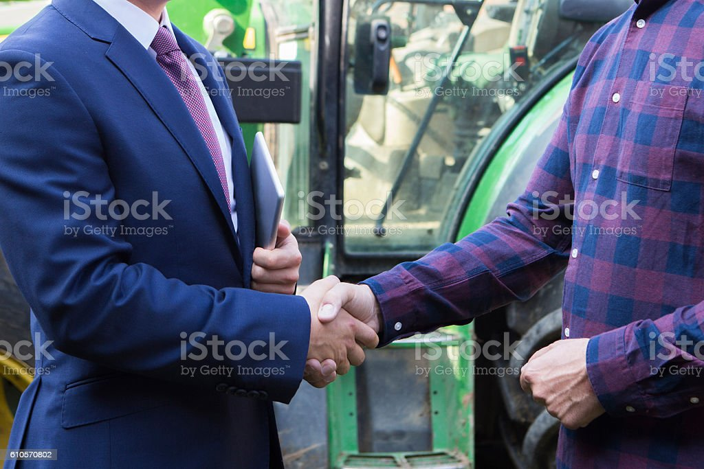 Farmer And Businessman Shaking Hands With Tractor In Background - foto stock