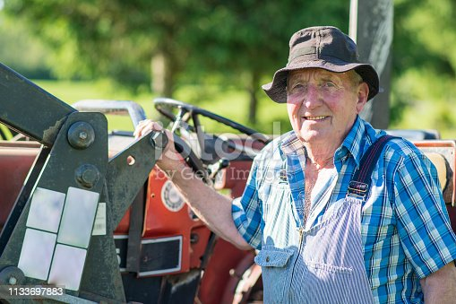 Smiling senior farmer sitting on a tractor in the sun as he is working on his farm. He is wearing a blue plaid shirt and coveralls.