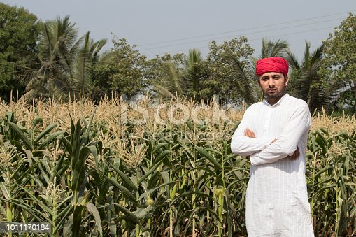 Portrait of farmer with arms crossed at corn field
