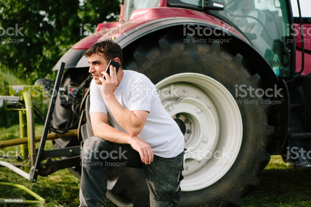 Farmer at the phone stands next to his tractor in a field zbiór zdjęć royalty-free