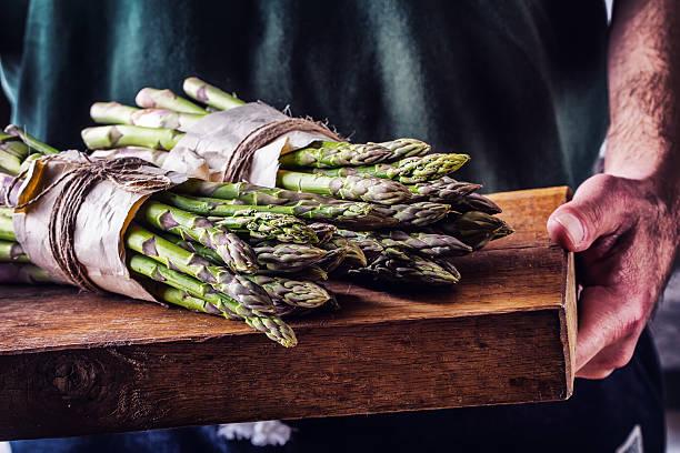 landwirt trägt die mit spargel auf einem hölzernen bord - spargel vegan stock-fotos und bilder