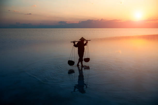 Farmer carrying baskets on the water. stock photo