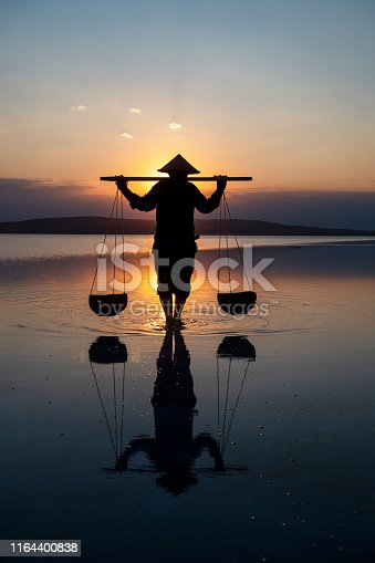 Farmer carrying baskets on the water.