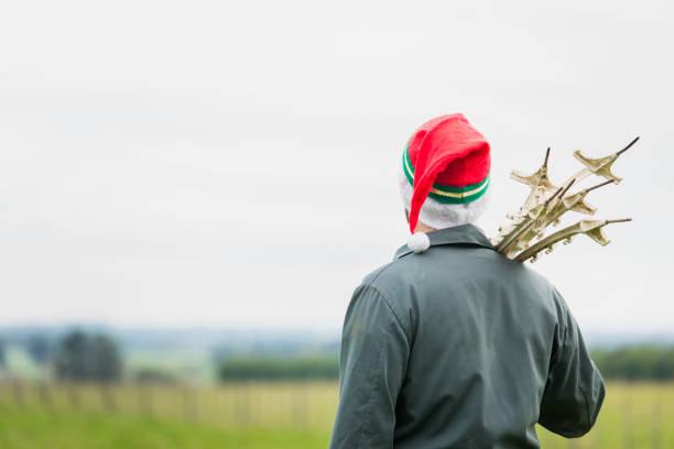 Landwirt Weihnachten - ein Mann steht im Feld tragen Overalls und Weihnachtsmütze Fechten Normen mit gedrückter – Foto
