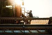 A farmer climbs up the ladder into his large combine grain harvester, ready to start a long day of work. The morning sun rises just behind him.  Shot in Worley, Idaho, USA.