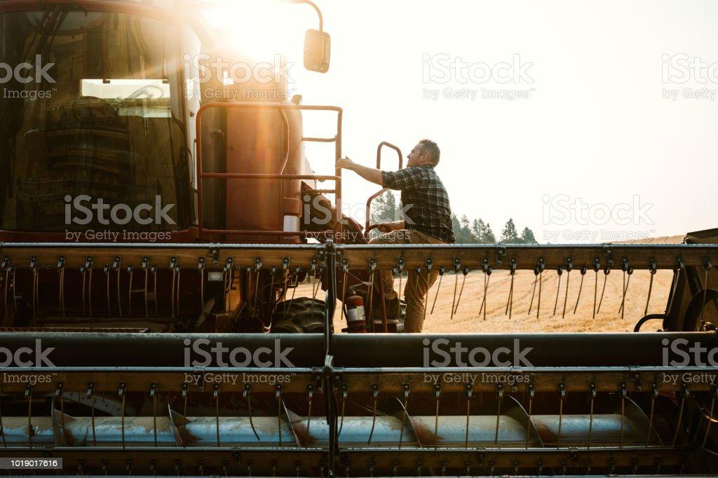 Farmer Climbing In To Combine Harvester In Idaho Wheat Field stock photo