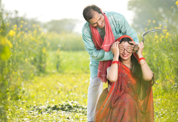 Farmer covering his wife's eyes on agricultural field Happy farmer covering his wife's eyes on agricultural field at village romance stock pictures, royalty-free photos & images