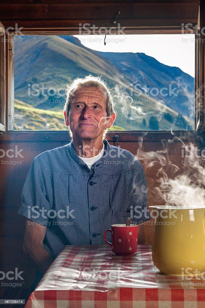 farmer drinking coffee in farmhouse, Switzerland stock photo