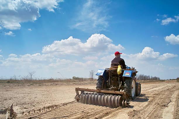 Farmer driving tractor plow field stock photo