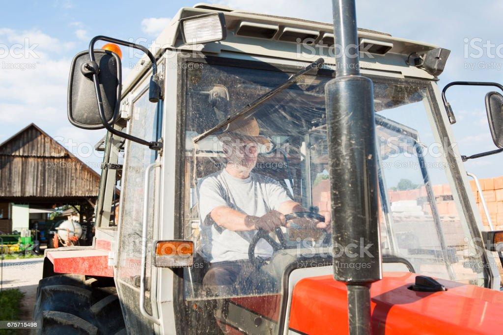 農民駕駛拖拉機用髒的擋風玻璃 免版稅 stock photo