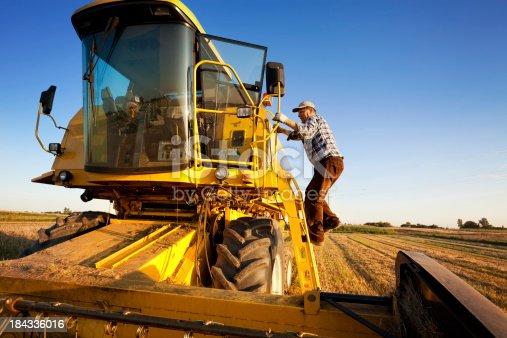 Farmer enters the combine harvester. Starts harvest.