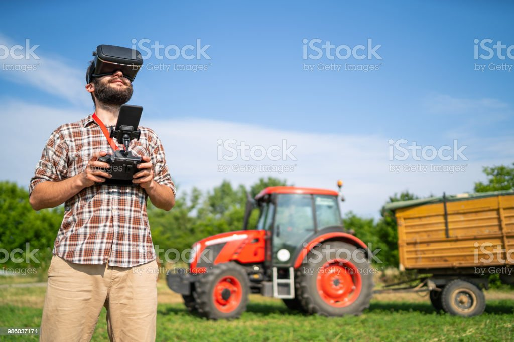 Farmer flying a drone over a field, and using VR headset stock photo
