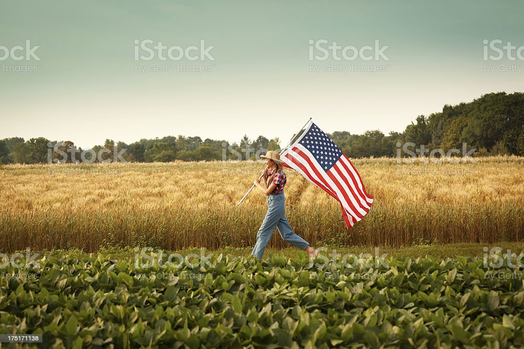 Farmer Girl Waving USA Flag Marching Across Summer Farm Field stock photo