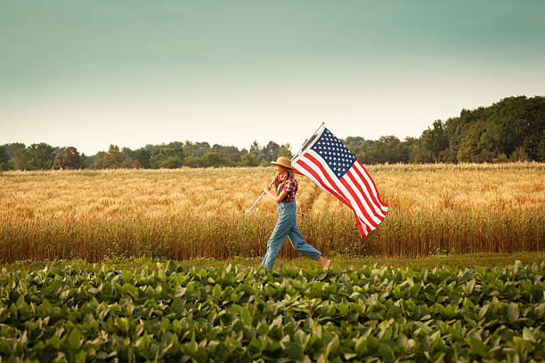 Farmer Girl Waving USA Flag Marching Across Summer Farm Field stock photo