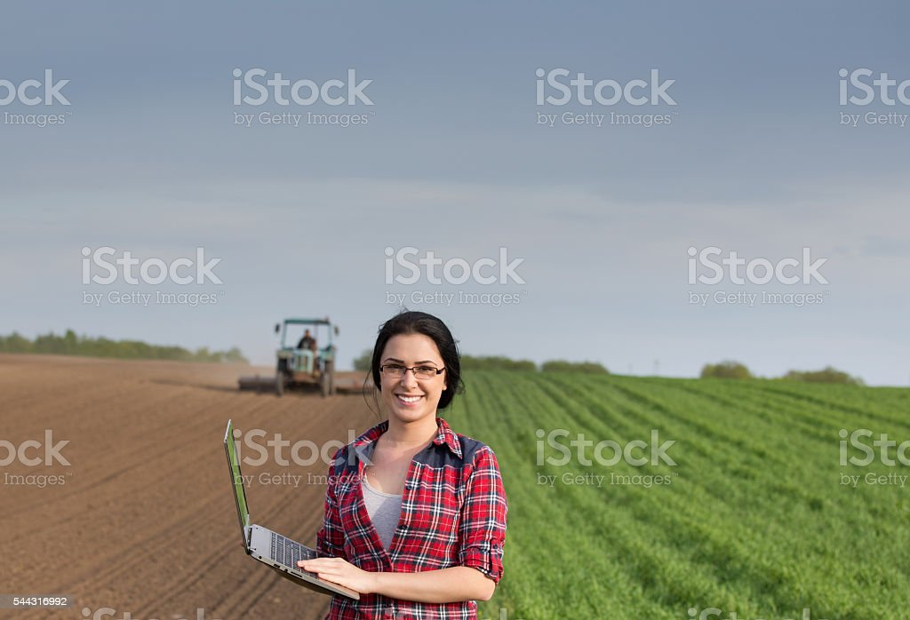 Farmer girl with laptop in field with tractor - Photo