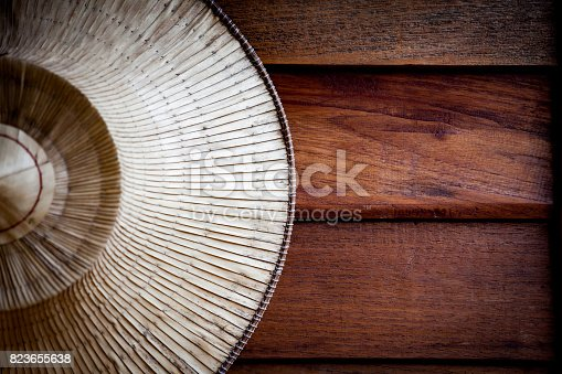 istock Farmer hat made of woven palm leaves hanging on antique rustic wooden background, copy space 823655638