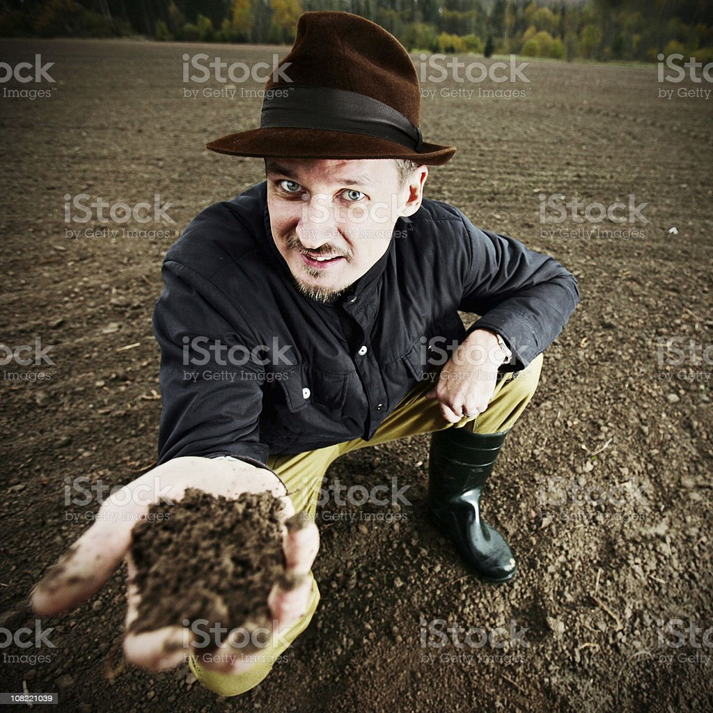 Farmer Holding up Dirt in Field royalty-free stock photo