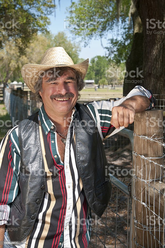 Farmer in a cowboy hat looking over his livestock stock photo