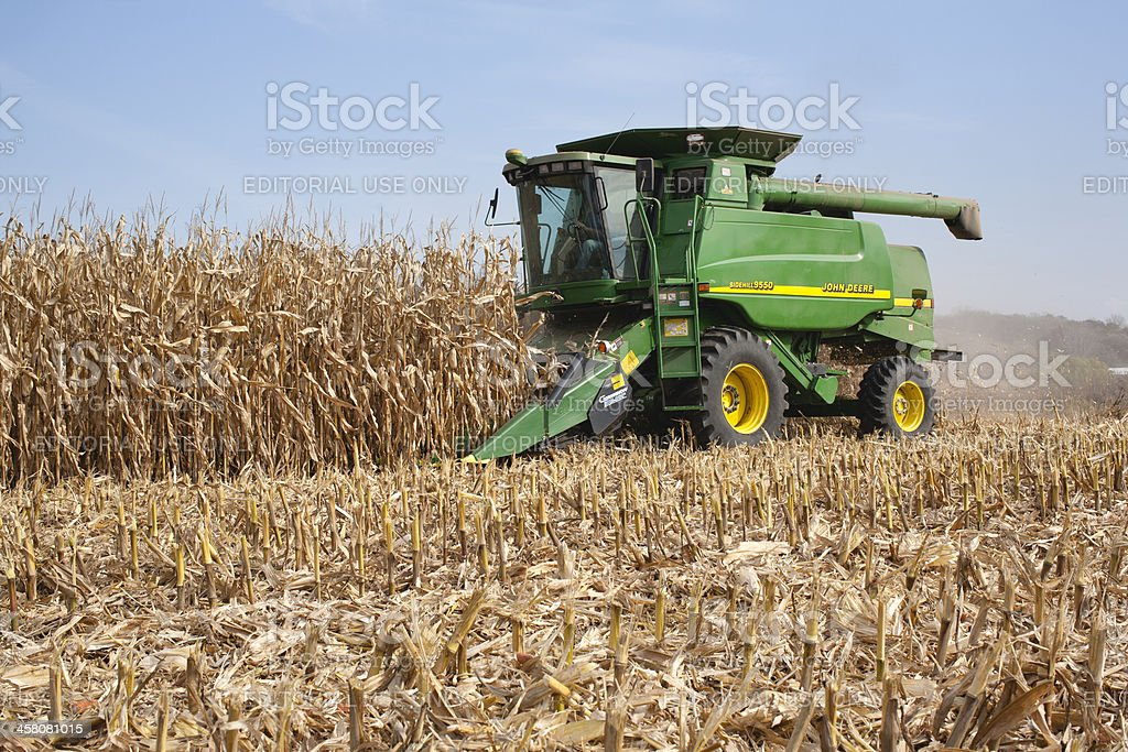 Farmer in a John Deere combine harvesting corn stock photo