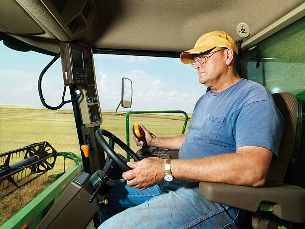 Farmer in combine harvesting crop. stock photo