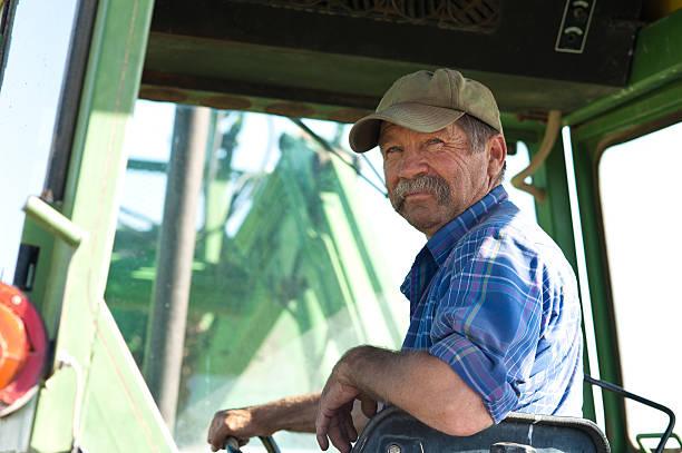 landwirt in seinem traktor - bauernberuf stock-fotos und bilder