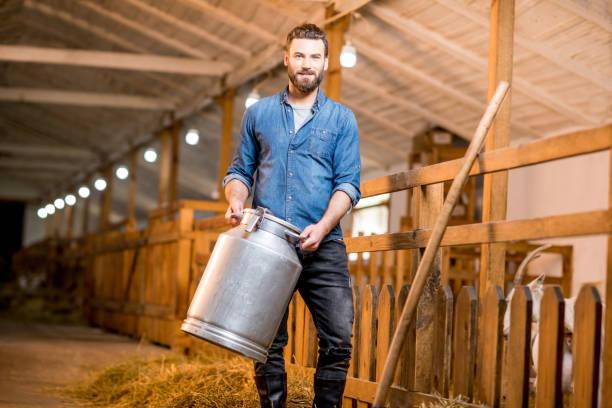 farmer in the goat barn - allevatore foto e immagini stock