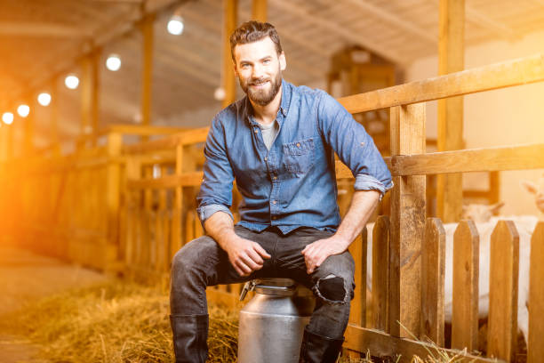 Farmer in the goat barn Portrait of a handsome farmer sitting on the retro milk container at the goat barn. Natural milk production and farming concept rancher stock pictures, royalty-free photos & images