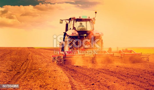 Farmer in tractor preparing land for sowing