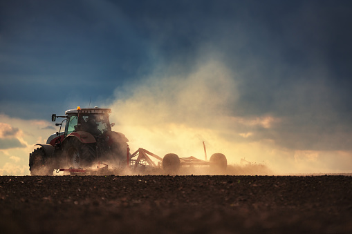 istock Farmer in tractor preparing land with seedbed cultivator 527889698