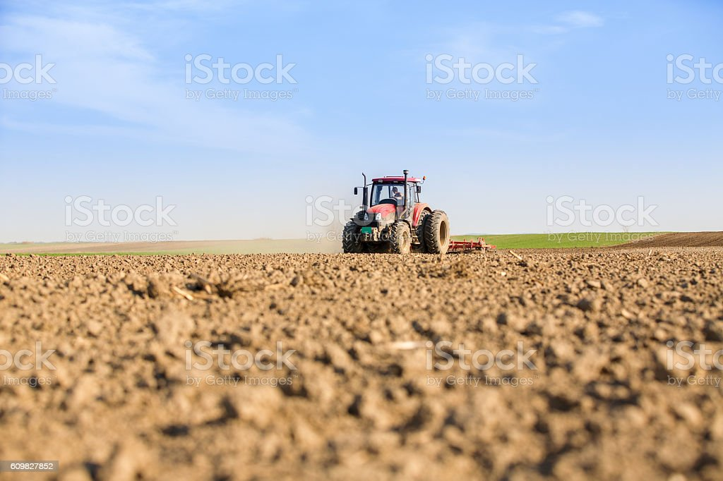 Farmer in tractor preparing land with seedbed cultivator. stock photo
