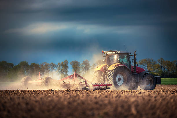 Farmer in tractor preparing land with seedbed cultivator Farmer in tractor preparing land with seedbed cultivator, sunset shot agricultural machinery stock pictures, royalty-free photos & images