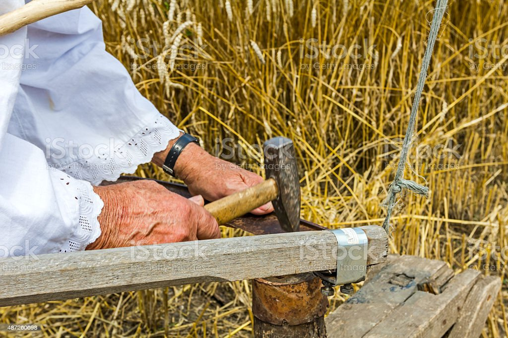 Farmer is sharpening, ironing, repair the blade on scythe. stock photo