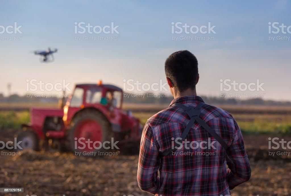 Farmer navigating drone above farmland stock photo