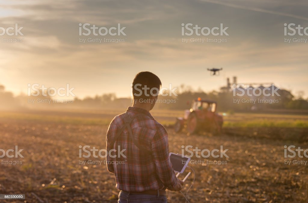 Farmer navigating drone above farmland stock photo