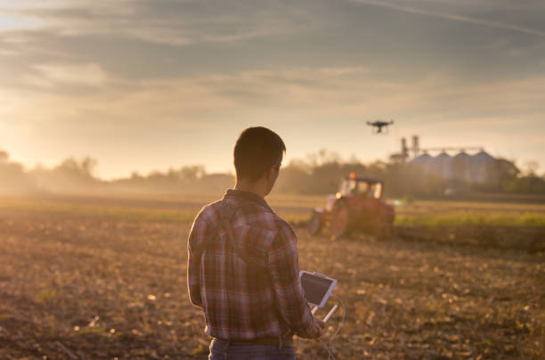 farmer navigating drone above farmland - drones stock photos and pictures
