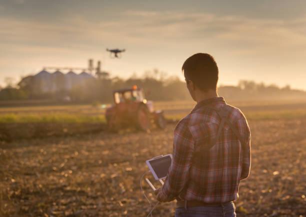 landwirt navigation drohne über ackerland - flugdrohne stock-fotos und bilder