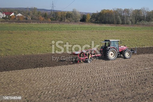 istock A farmer on a red tractor with a seeder sows grain in plowed land in a private field in the village area. Mechanization of spring field work. Farmer's everyday life. Processing of land. The agrarian. 1097546346