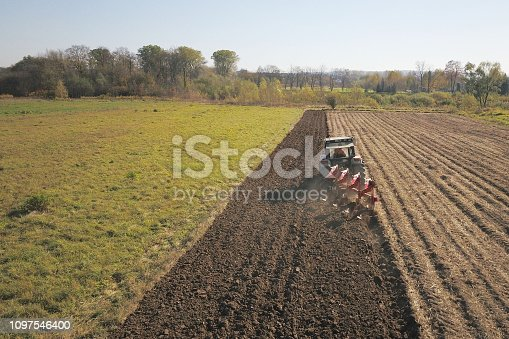 istock A farmer on a red tractor with a seeder sows grain in plowed land in a private field in the village area. Mechanization of spring field work. Farmer's everyday life. Processing of land. The agrarian. 1097546400