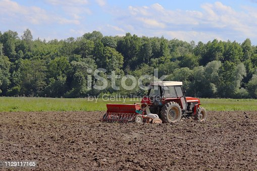 istock A farmer on a red tractor with a seeder sows grain in plowed land in a private field in the village area. Mechanization of spring field work. Farmer's everyday life. Processing of land. The agrarian. 1129117165