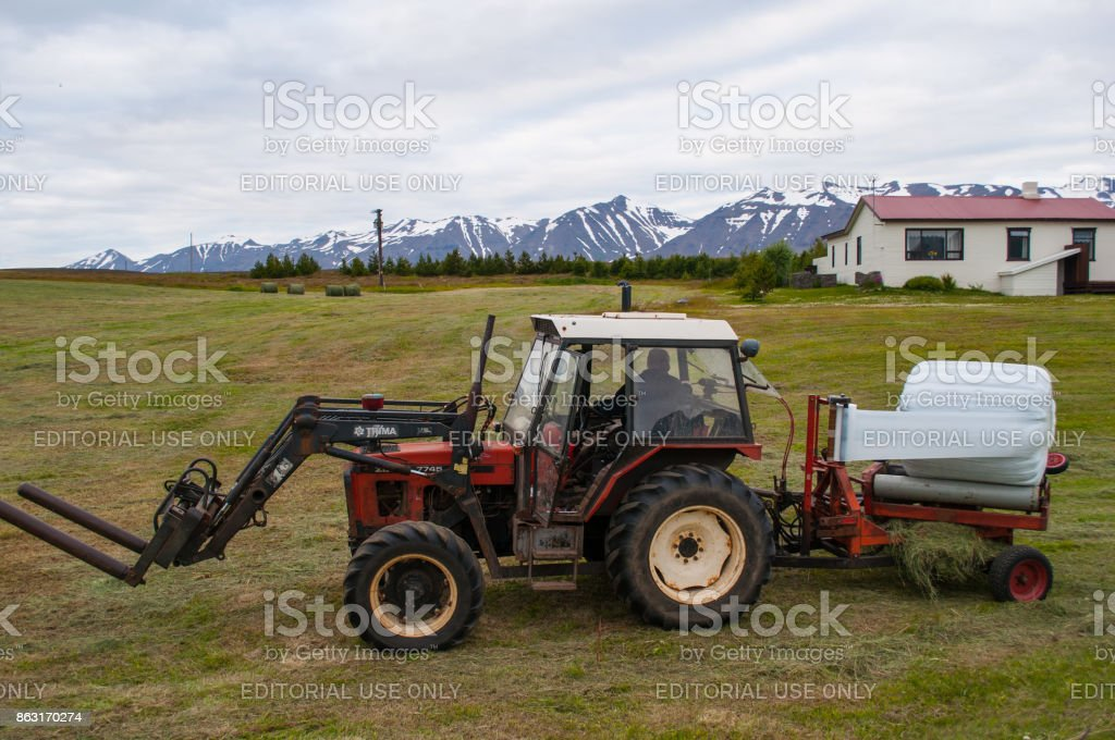 Farmer on a tractor wrapping hey bales stock photo