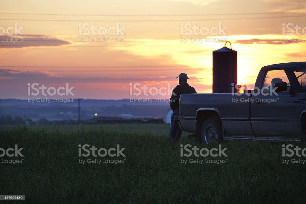 A farmer on his truck watching a sunset stock photo