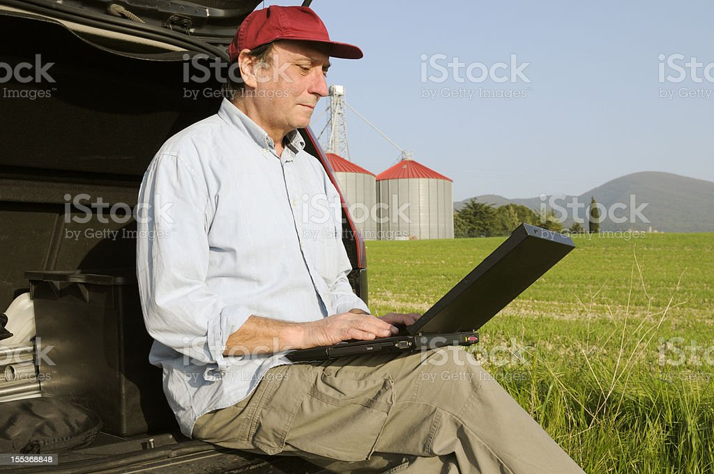 Farmer Planning PC in the Countryside royalty-free stock photo