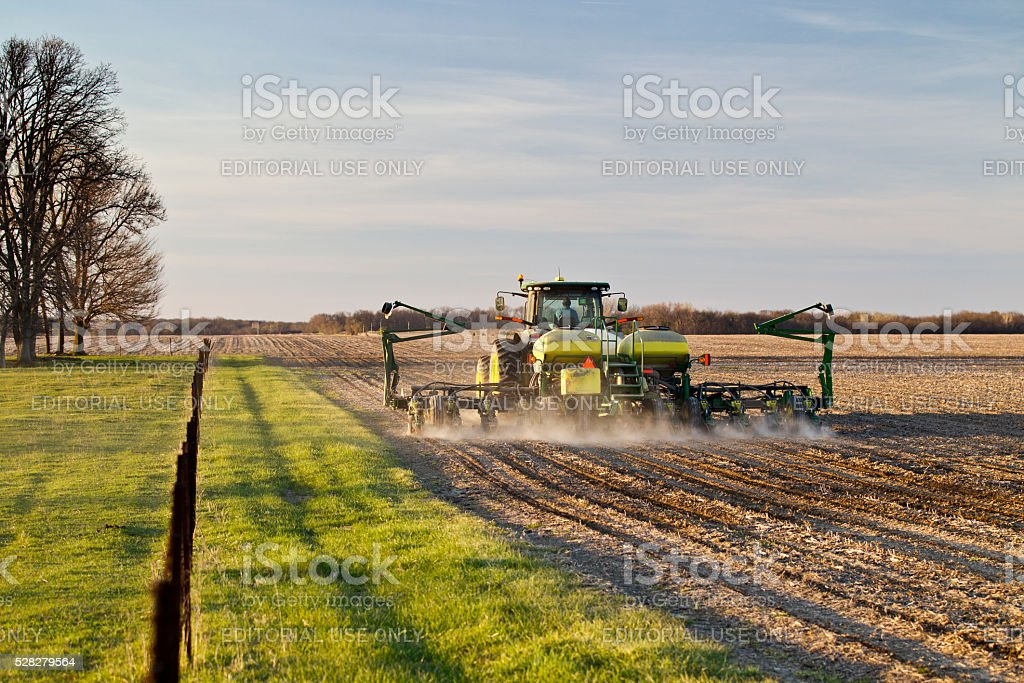 Farmer plants corn in central Illinois in early evening stock photo