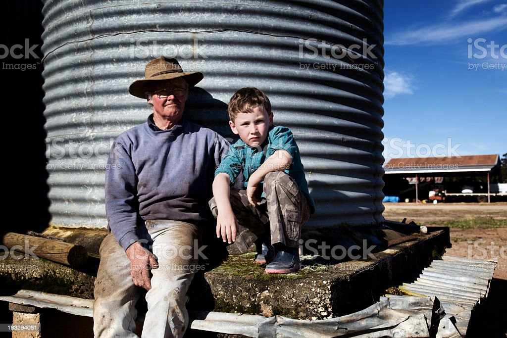 Farmer posing with grandson on farm  stock photo