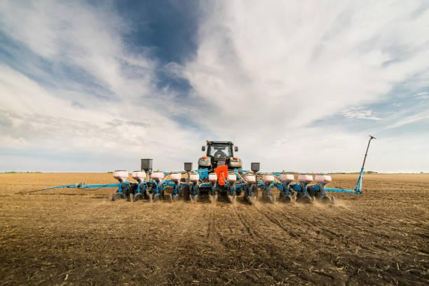 farmer seeding crops at field - piantare foto e immagini stock