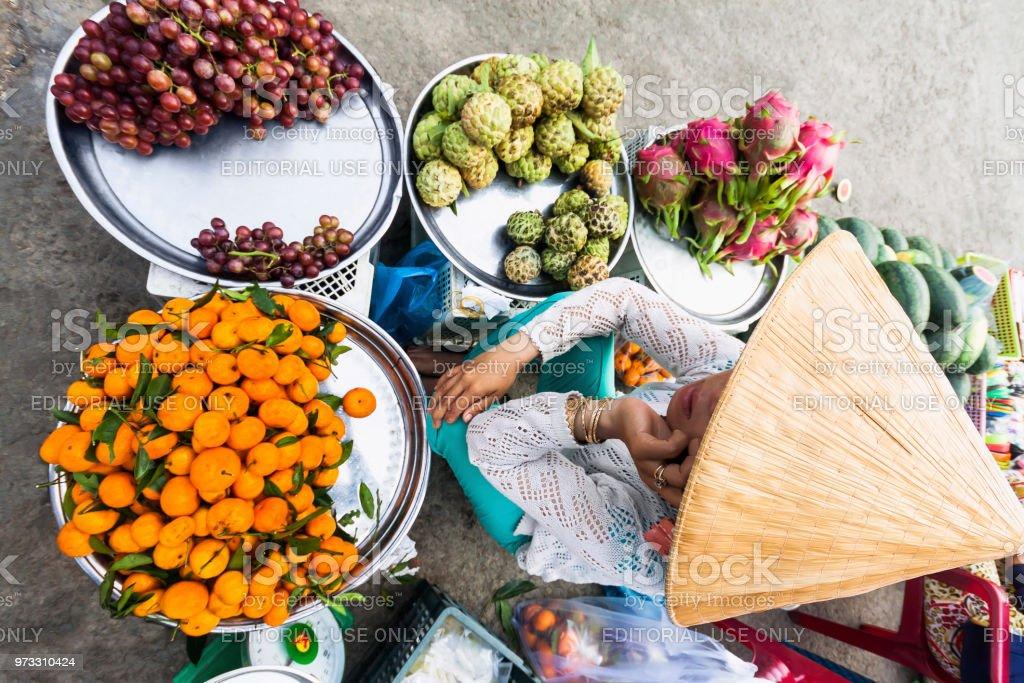 A farmer selling fresh fruit on the market - Ho Chi Minh City, Vietnam stock photo