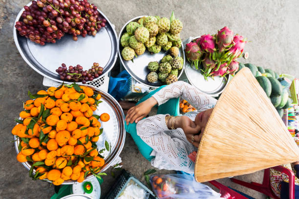 A farmer selling fresh fruit on the market - Ho Chi Minh City, Vietnam stock photo
